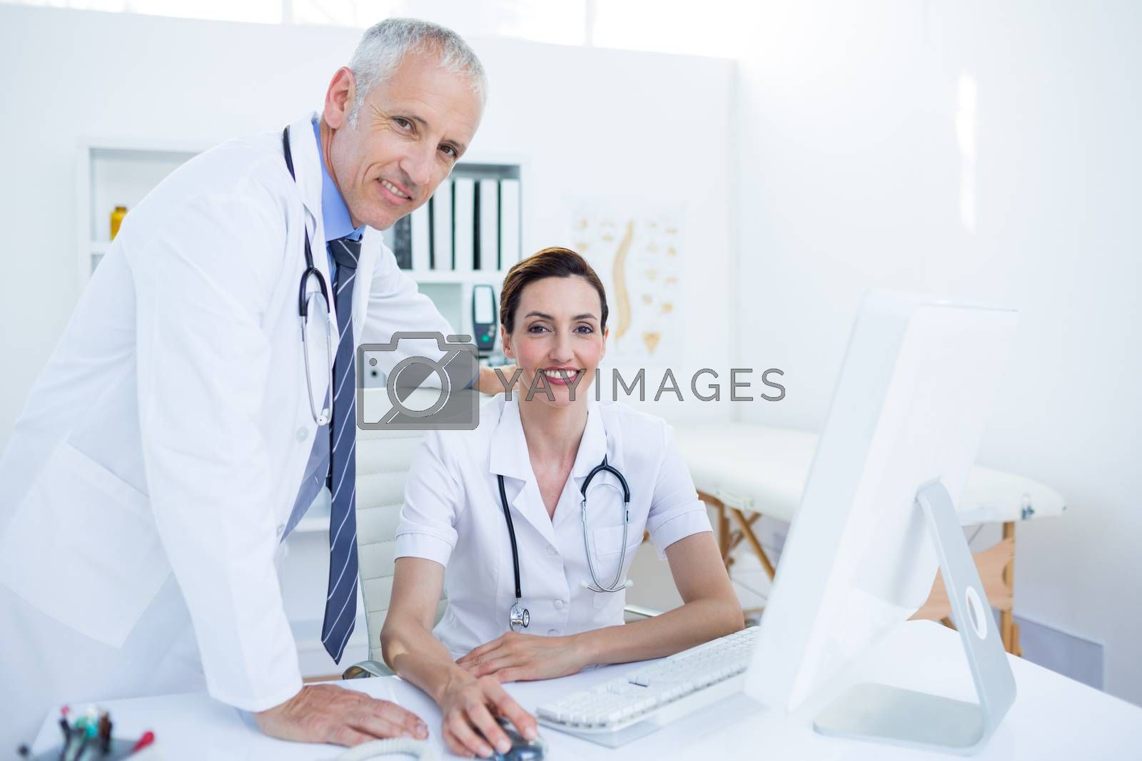 Royalty free image of Portrait of smiling medical colleagues working with computer and looking at camera by Wavebreakmedia