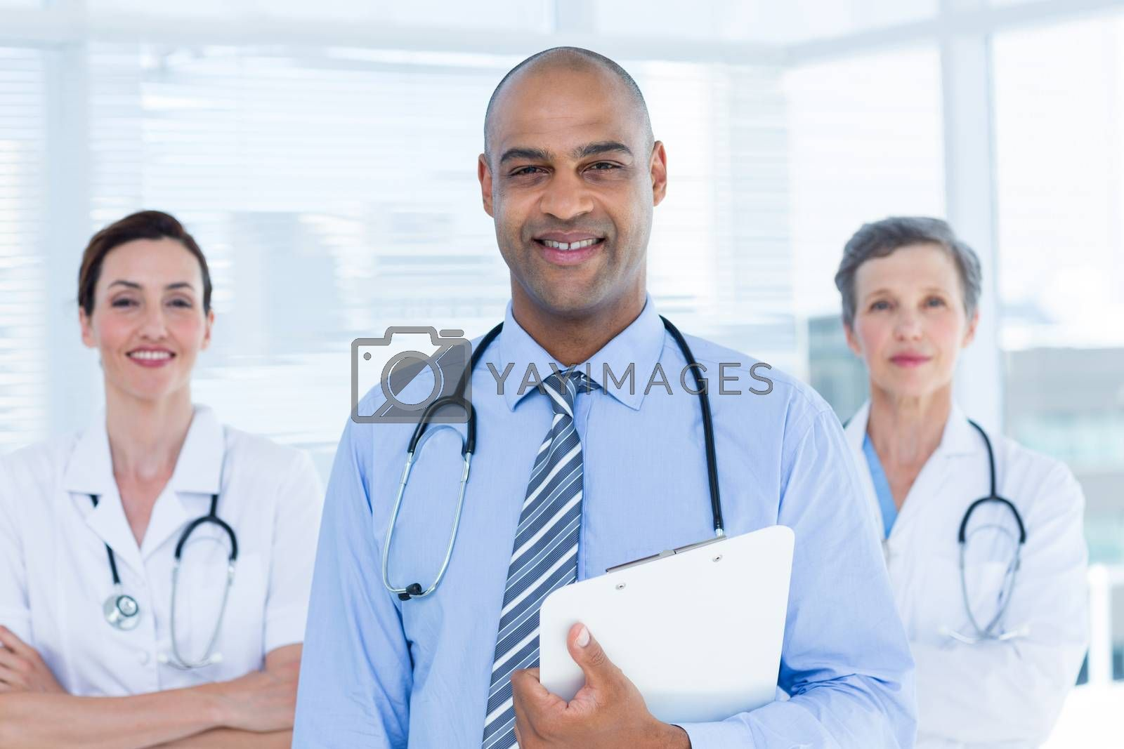 Royalty free image of Portrait of smiling doctor holding file and standing in front of his colleagues by Wavebreakmedia