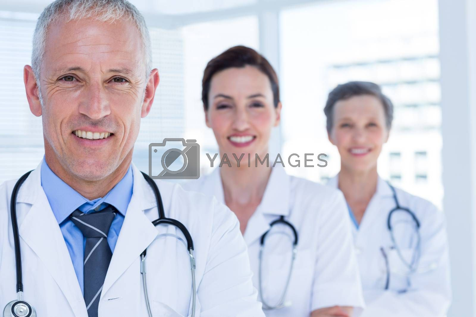 Royalty free image of Portrait of three smiling medical colleagues looking at camera by Wavebreakmedia