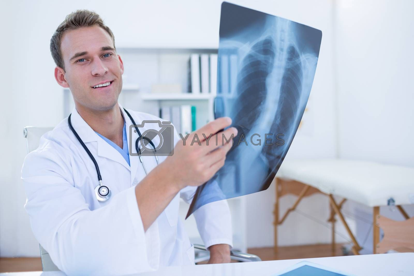 Royalty free image of Serious doctor looking at Xray  by Wavebreakmedia