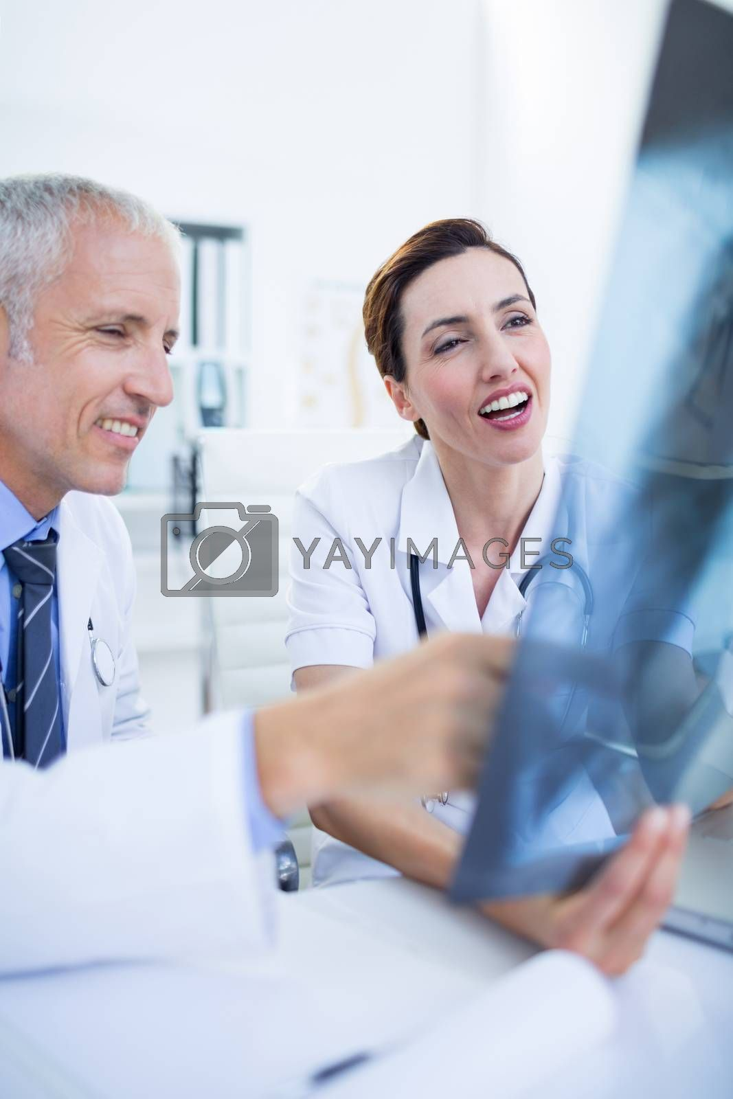 Royalty free image of Smiling medical colleagues examining x-ray together by Wavebreakmedia