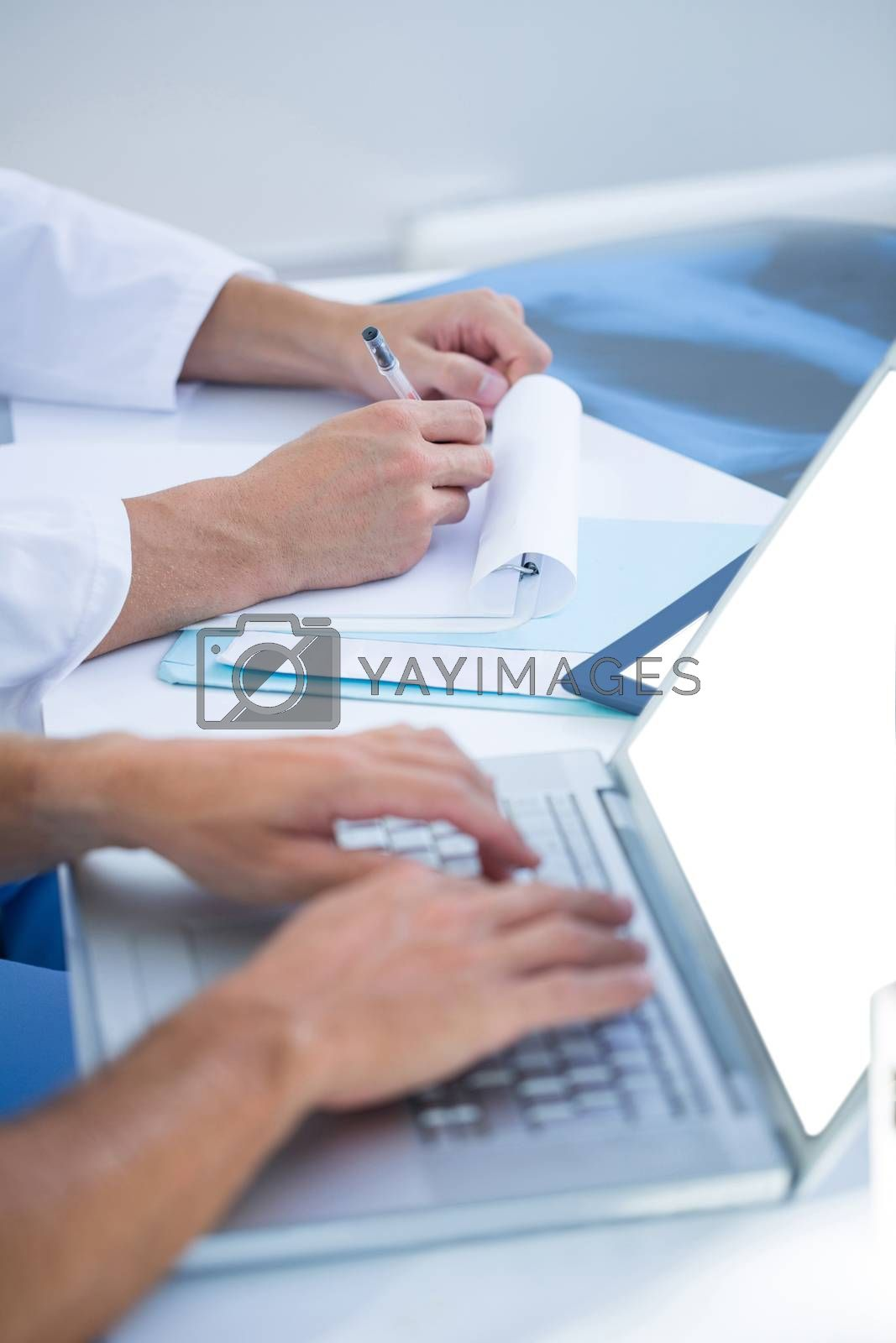 Royalty free image of Medical colleagues working with laptop and taking notes by Wavebreakmedia