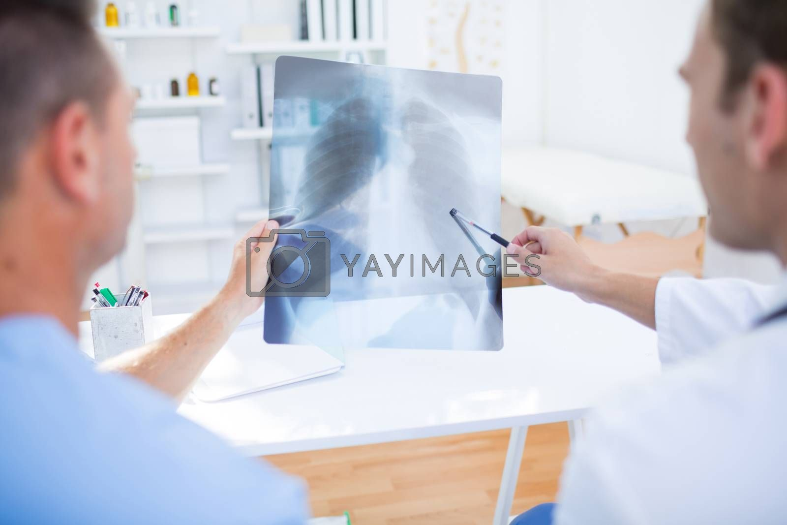 Royalty free image of Rear view of concentrated medical colleagues examining x-ray together by Wavebreakmedia