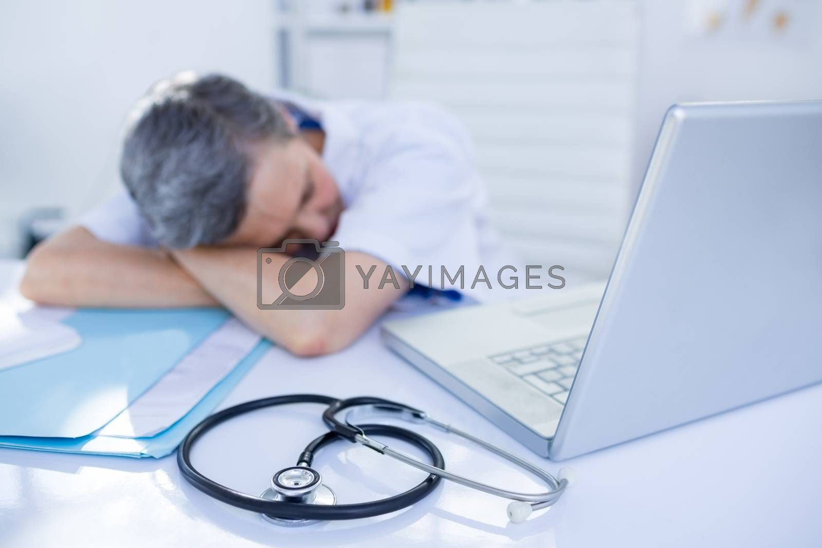 Royalty free image of Female doctor sleeping on desk  by Wavebreakmedia