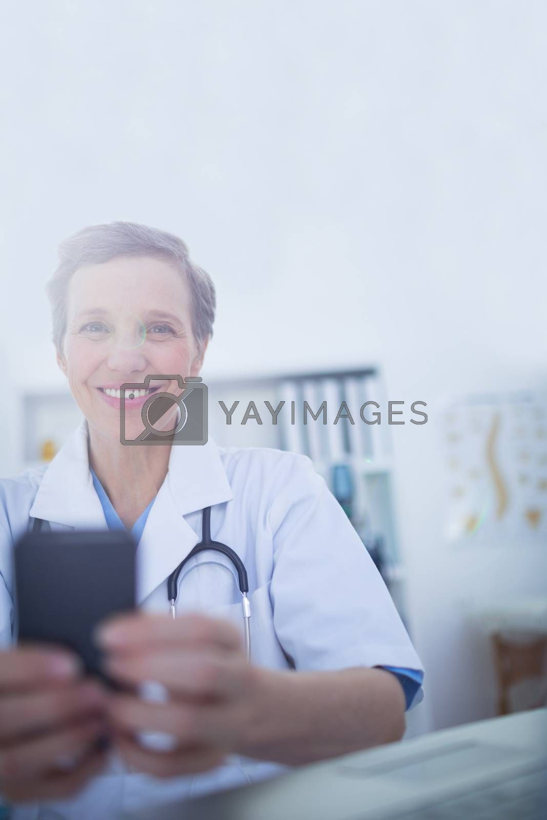 Royalty free image of Happy doctor looking at camera and using her smartphone  by Wavebreakmedia