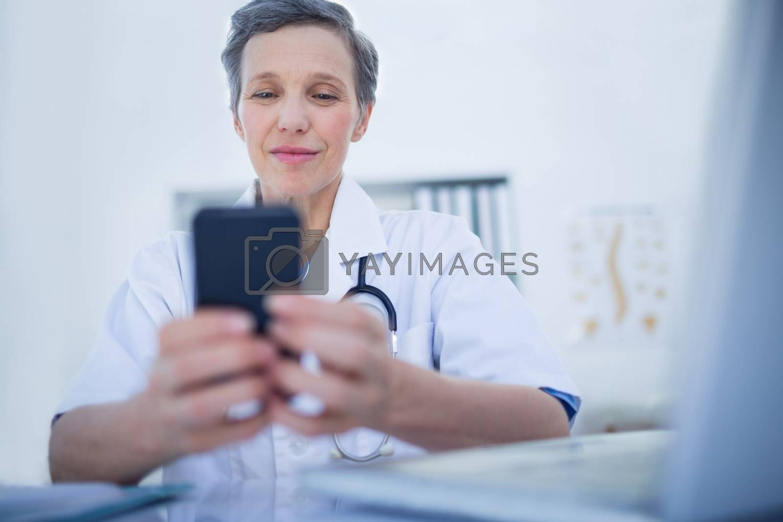 Royalty free image of Happy doctor using her smartphone  by Wavebreakmedia