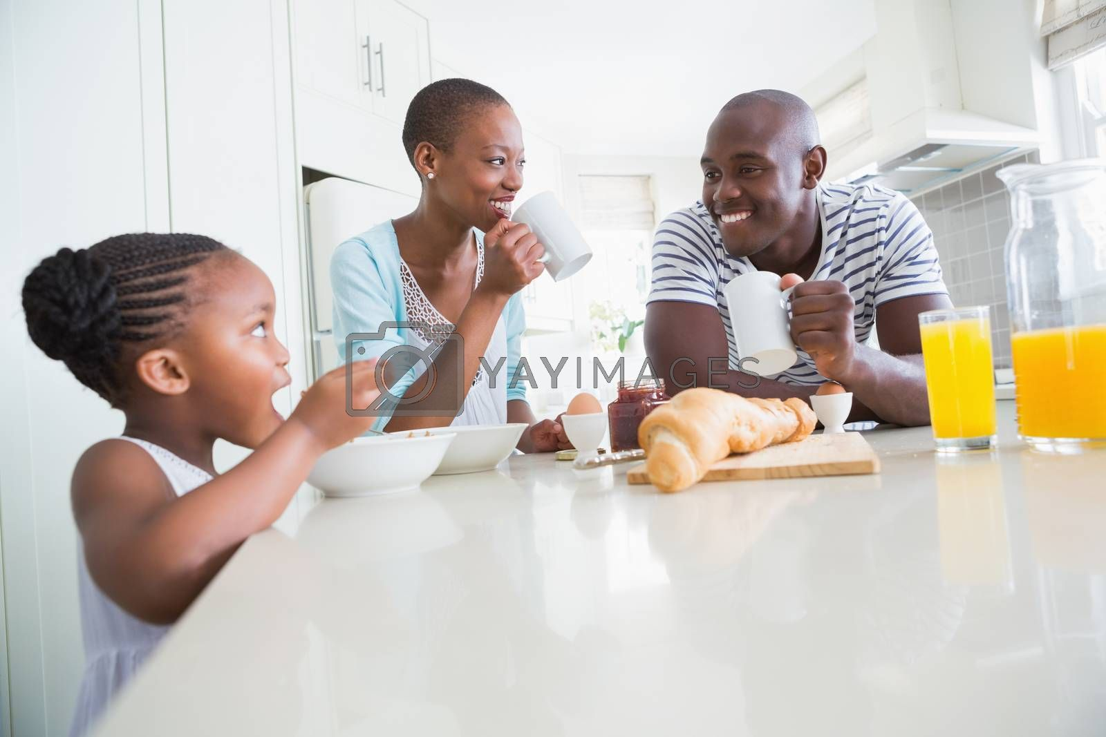 Royalty free image of Happy family sitting and taking breakfast by Wavebreakmedia