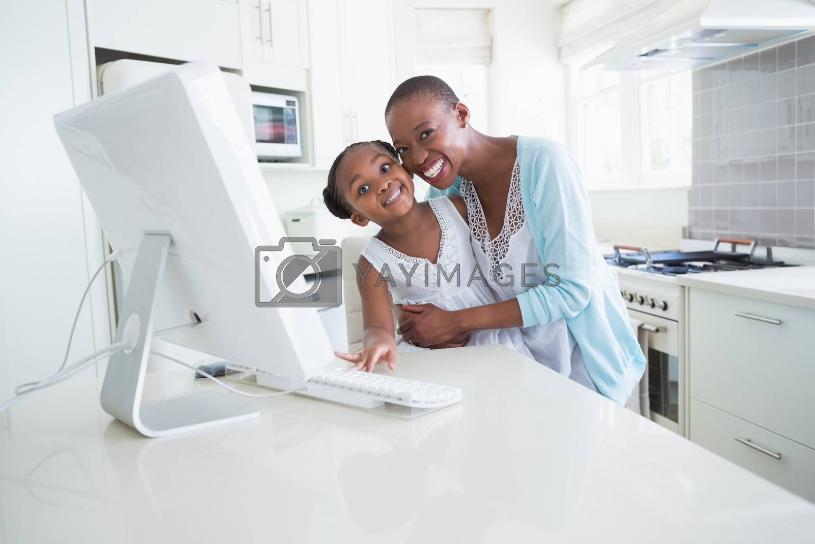 Royalty free image of Happy smiling mother with her daughter using computer  by Wavebreakmedia
