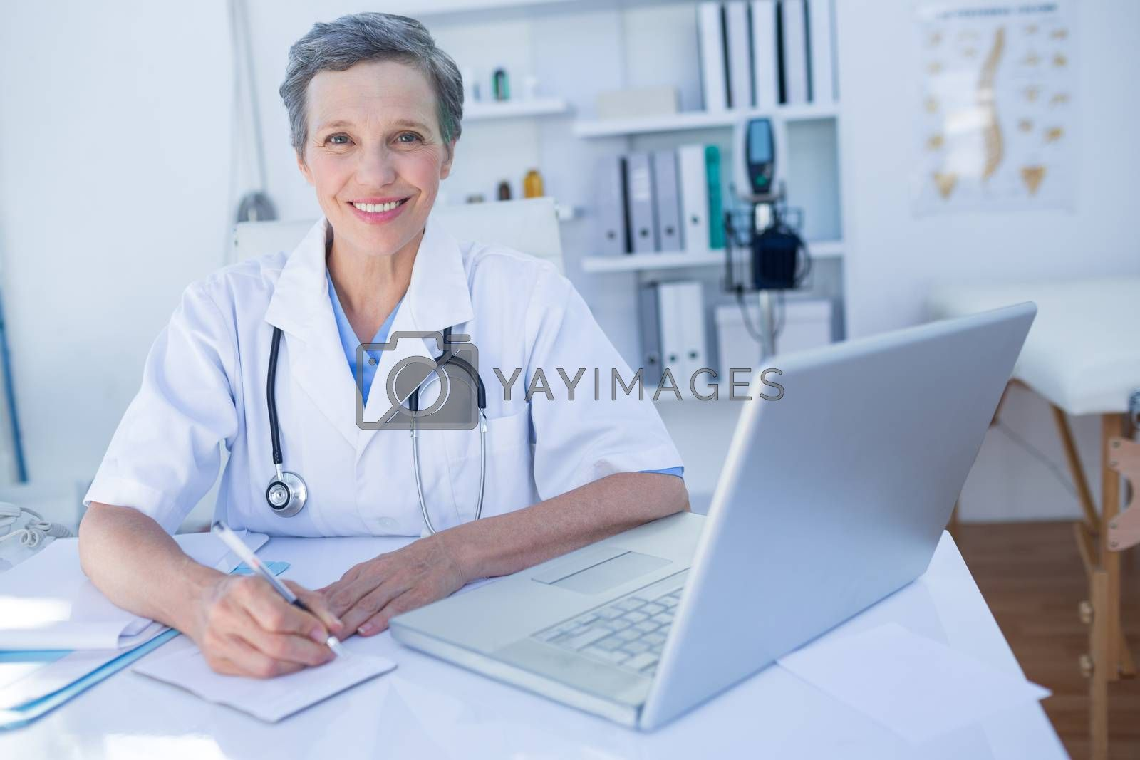 Royalty free image of Happy doctor looking at camera and writing on clipboard  by Wavebreakmedia