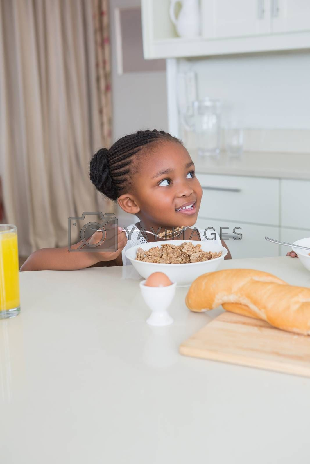 Royalty free image of Smiling beautiful little girl eating cereals  by Wavebreakmedia
