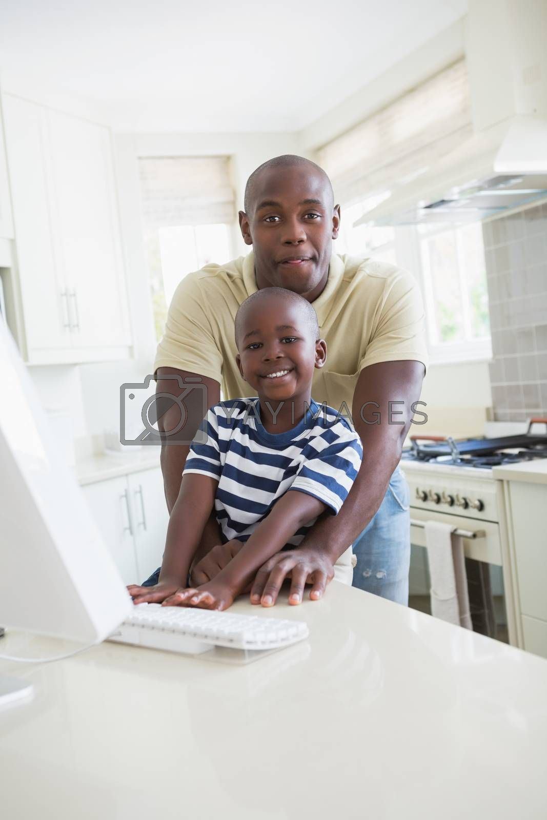 Royalty free image of Happy smiling father with his son using computer  by Wavebreakmedia
