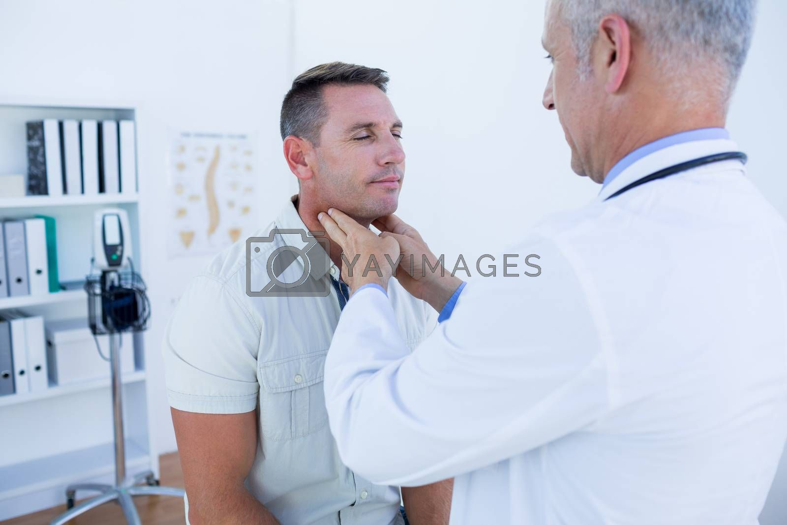 Royalty free image of Doctor examining his patient neck  by Wavebreakmedia