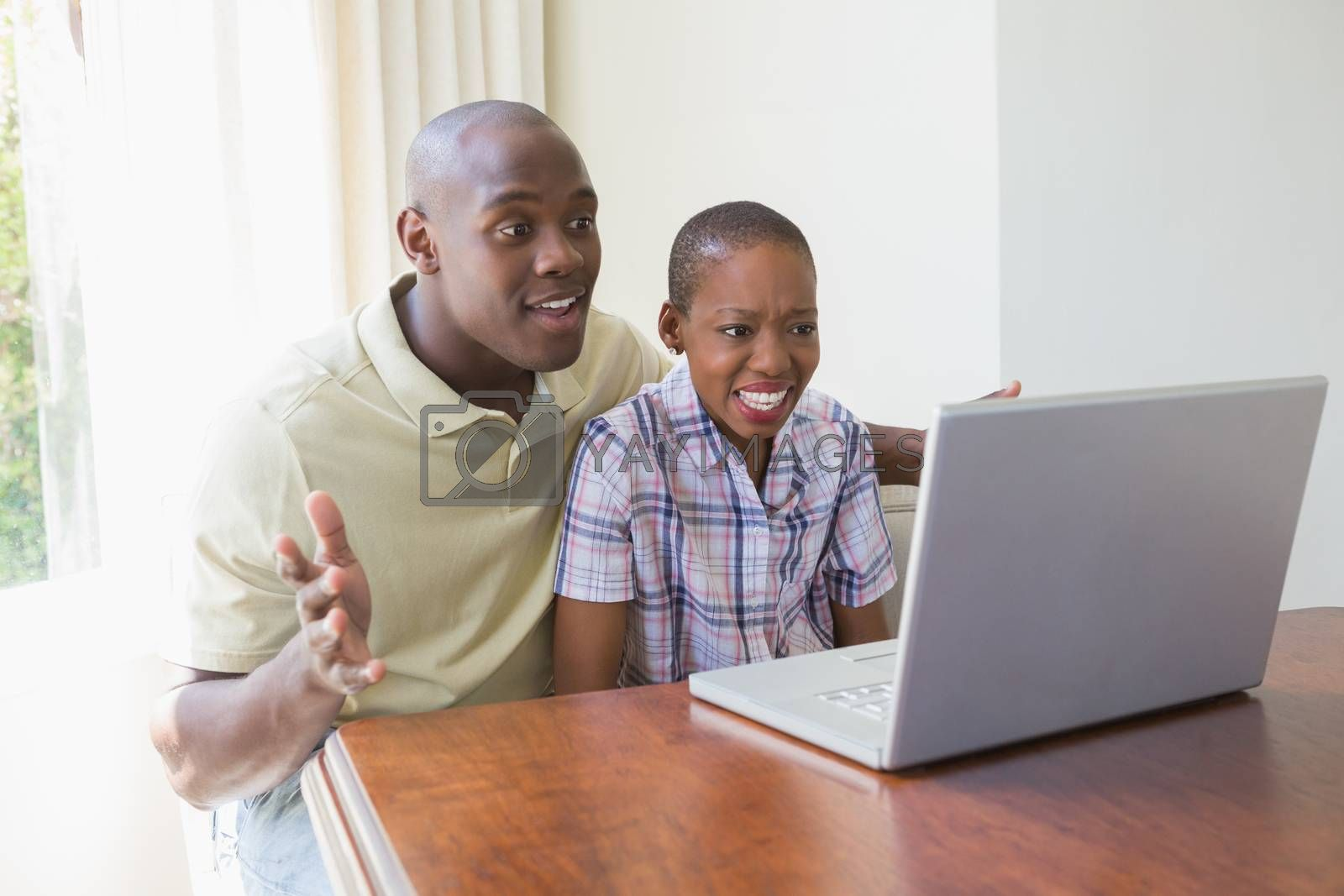 Royalty free image of Happy smiling couple using their laptop by Wavebreakmedia
