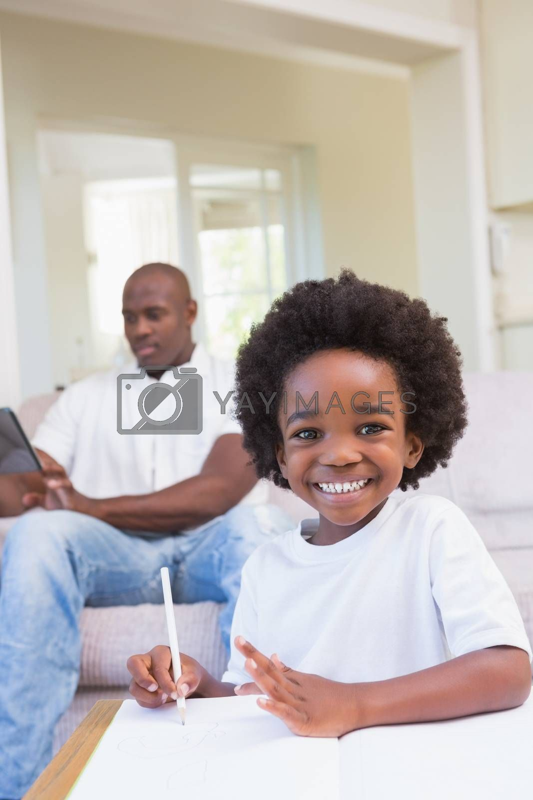 Royalty free image of Smiling little boy writing on table  by Wavebreakmedia