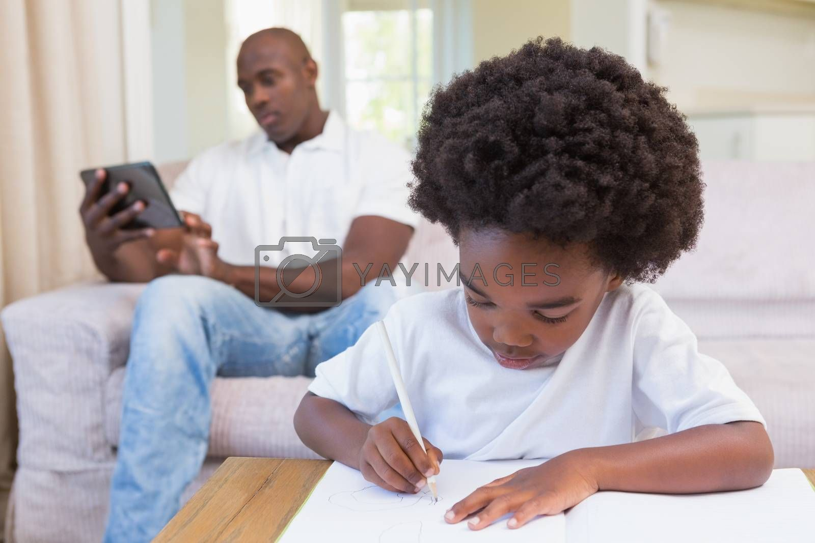 Royalty free image of A little boy writing on notepad by Wavebreakmedia