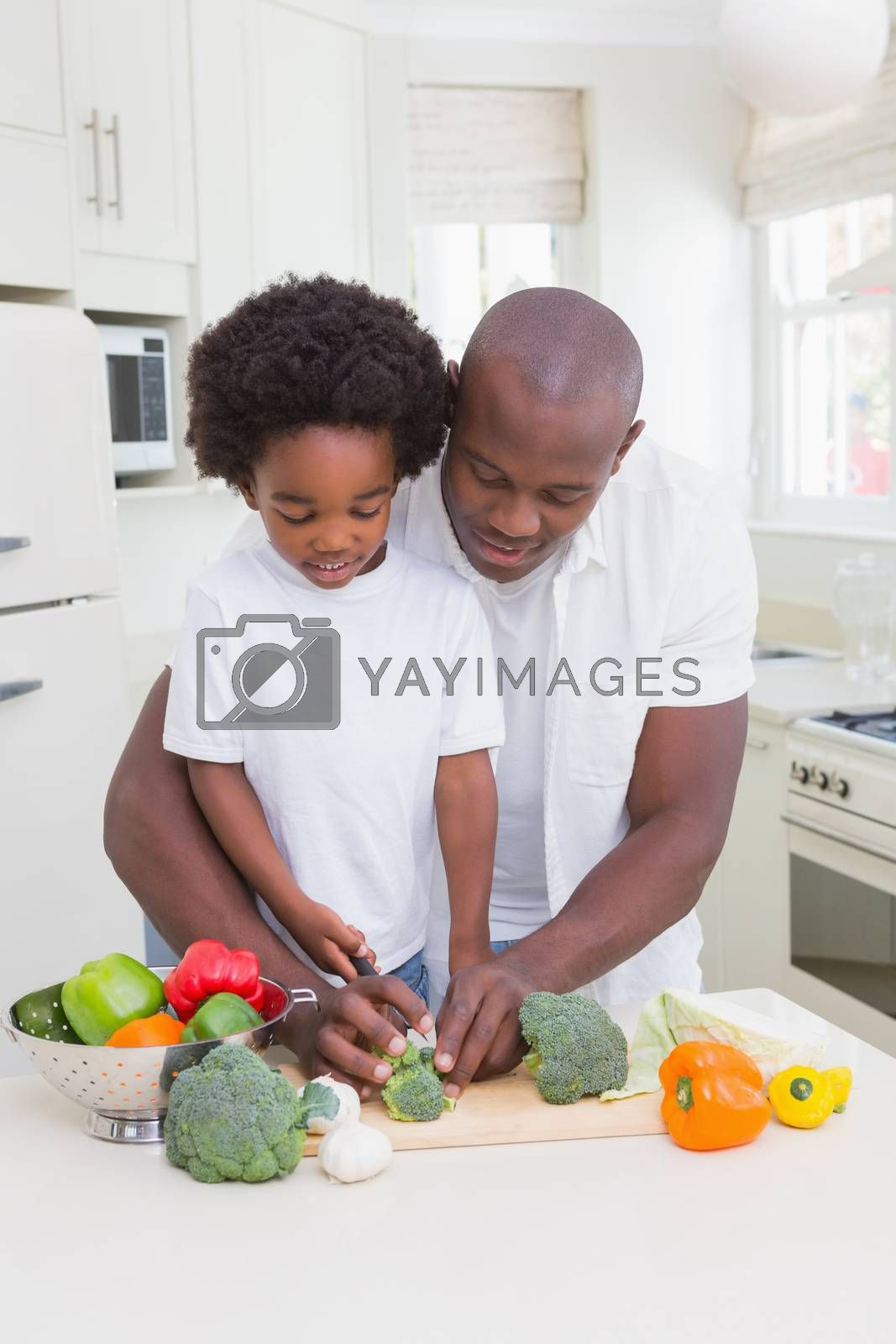 Royalty free image of Little boy cooking with his father by Wavebreakmedia