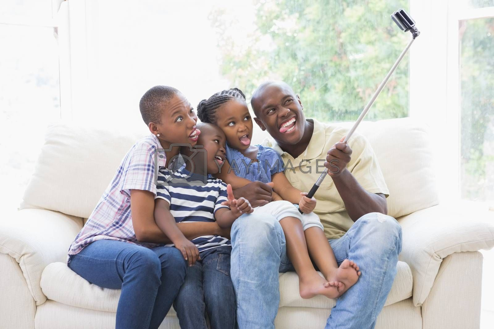 Royalty free image of Happy family on the couch taking a selfie  by Wavebreakmedia