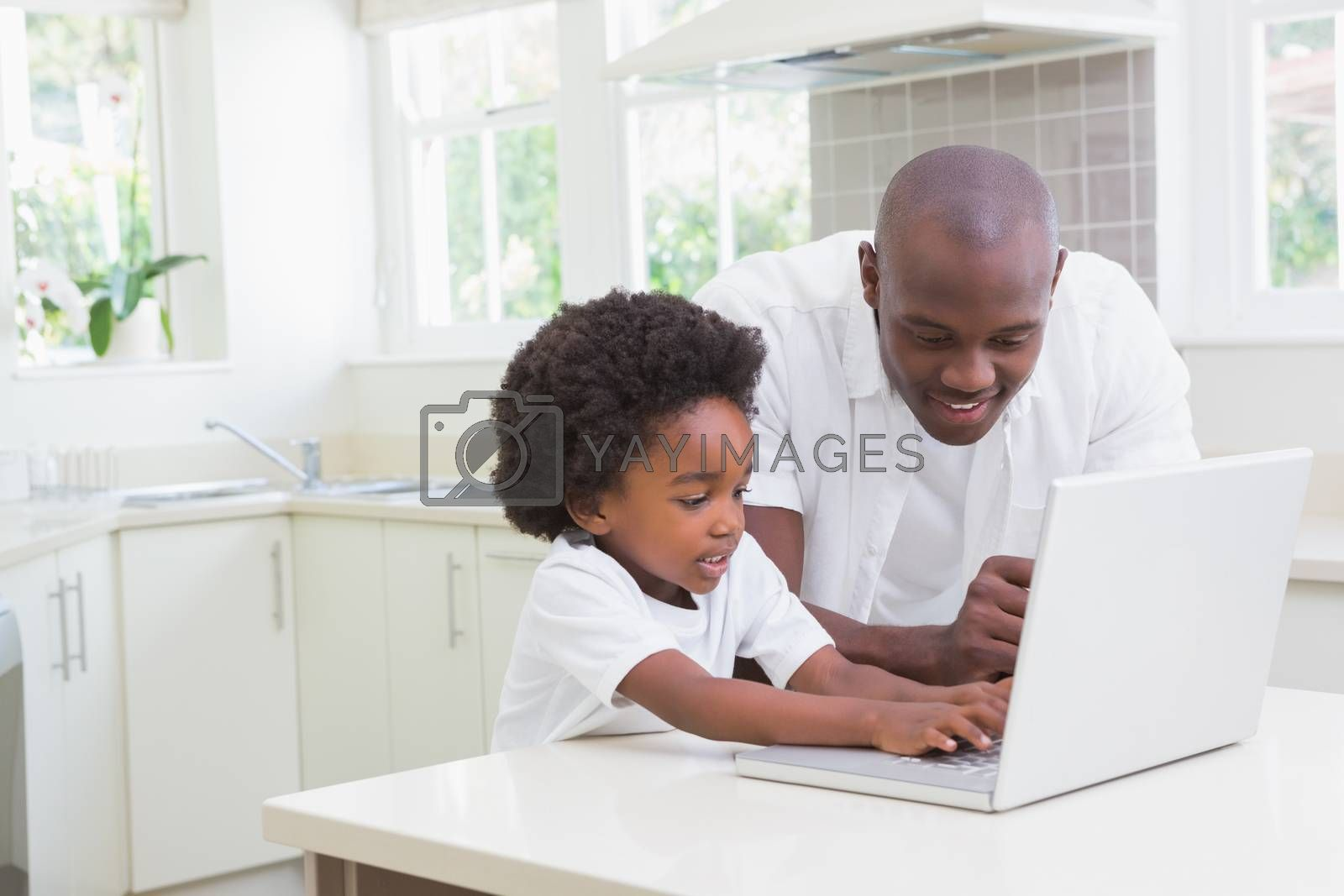 Royalty free image of Little boy using a laptop with his father  by Wavebreakmedia