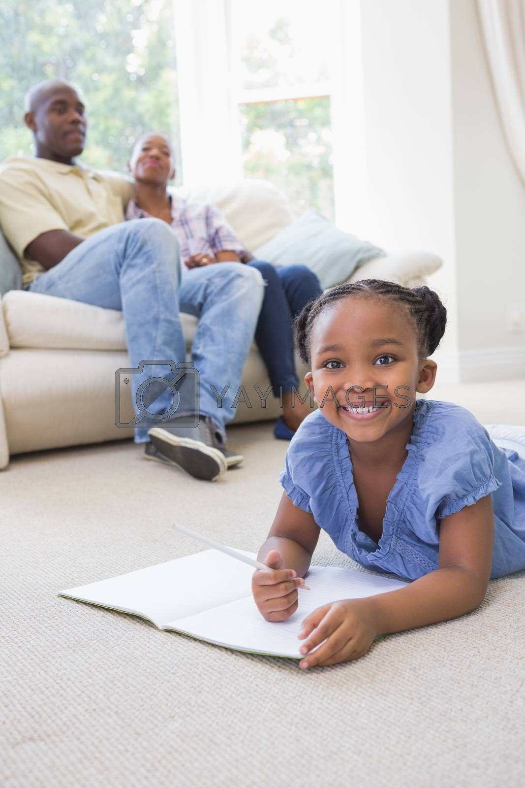 Royalty free image of Portrait happy smiling little girl writting on notepad  by Wavebreakmedia