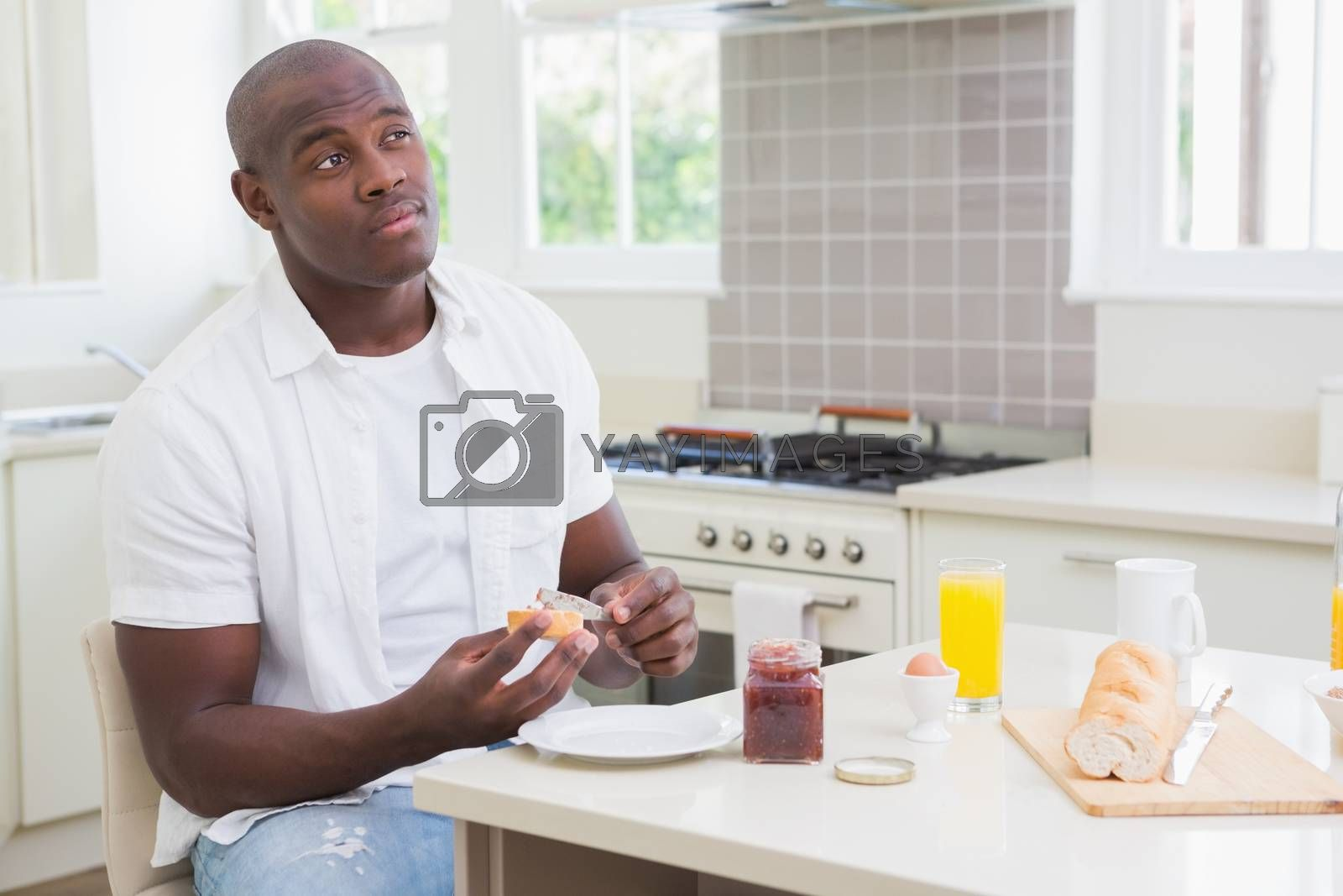 Royalty free image of Smiling man taking his breakfast  by Wavebreakmedia