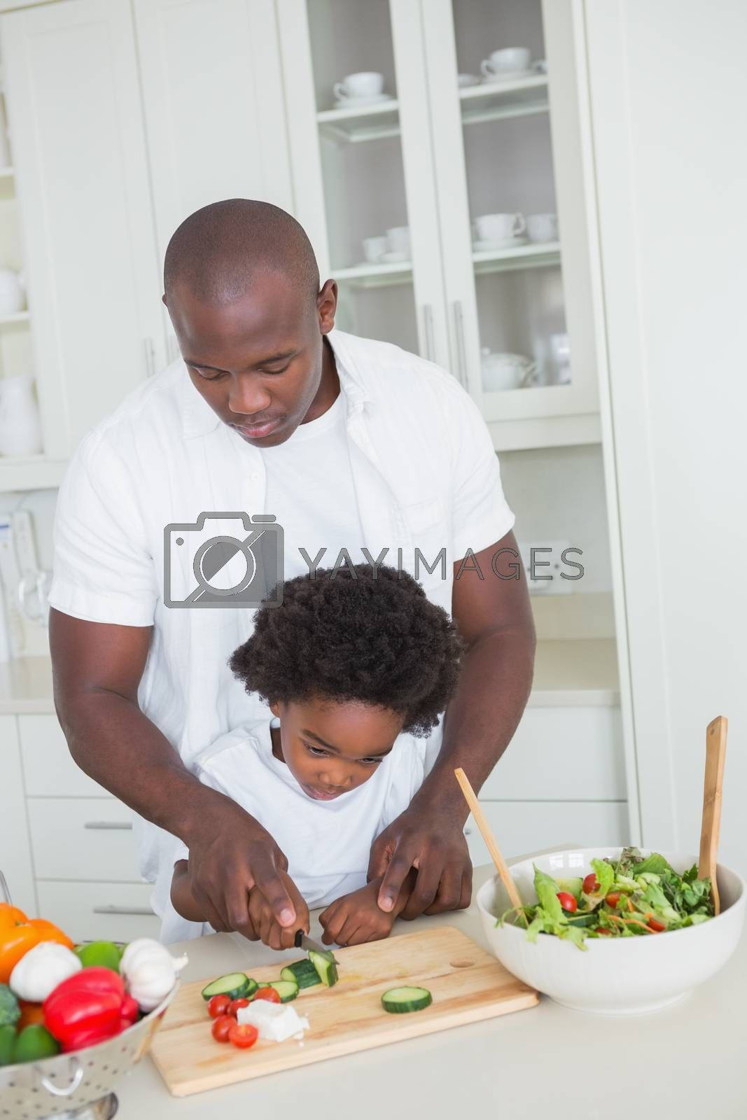 Royalty free image of Happy father and son preparing vegetables  by Wavebreakmedia