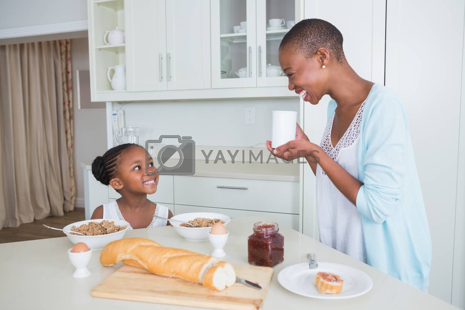Royalty free image of Smiling mother and daughter eating together  by Wavebreakmedia