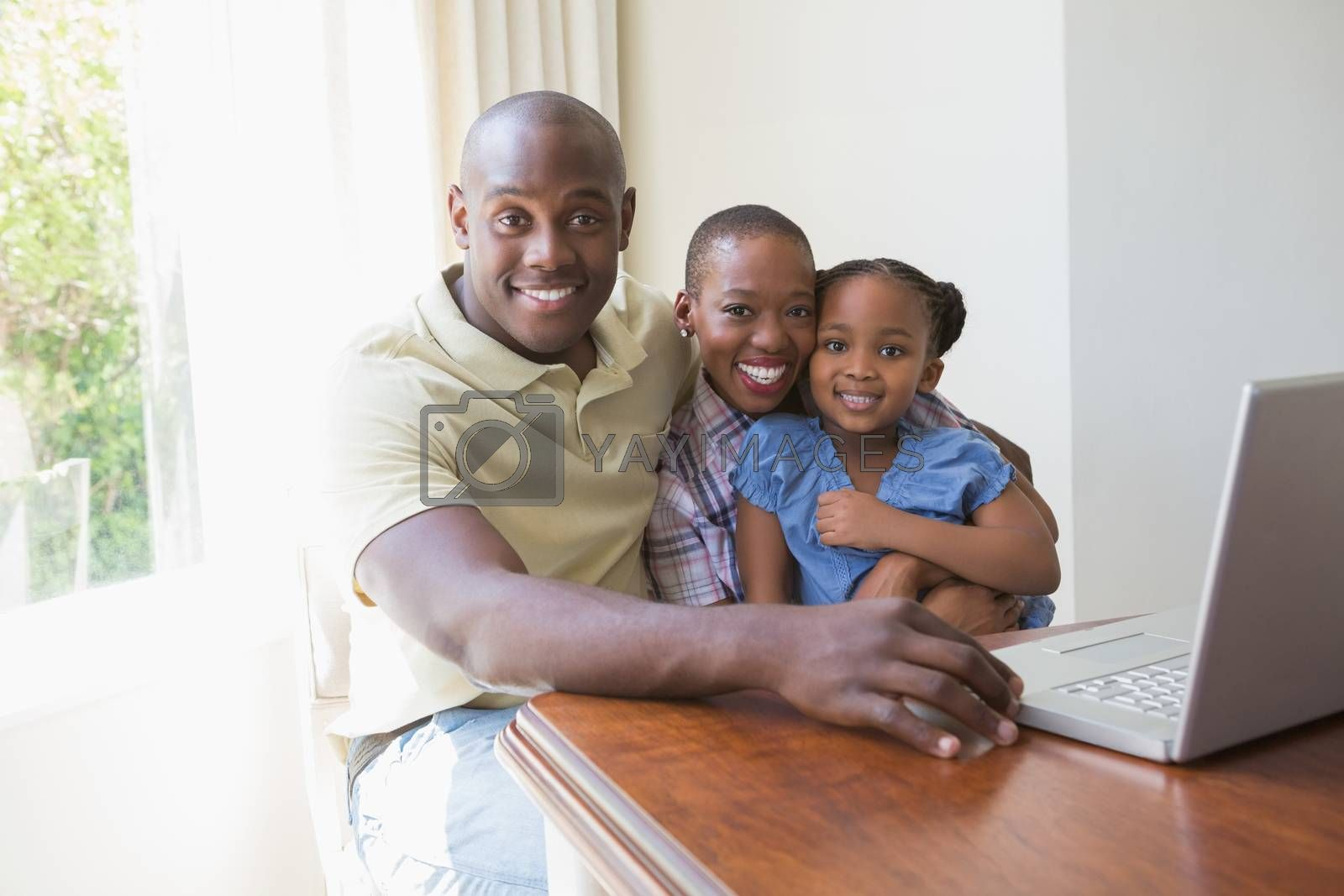 Royalty free image of Happy smiling family using laptop by Wavebreakmedia