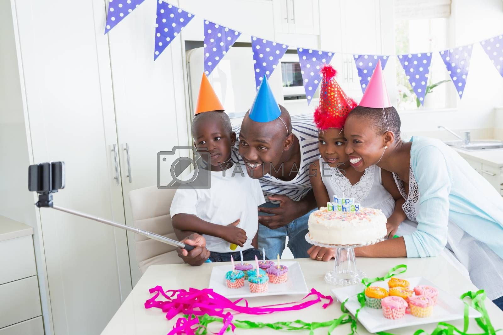 Royalty free image of Happy family celebrating a birthday together and taking a selfie by Wavebreakmedia
