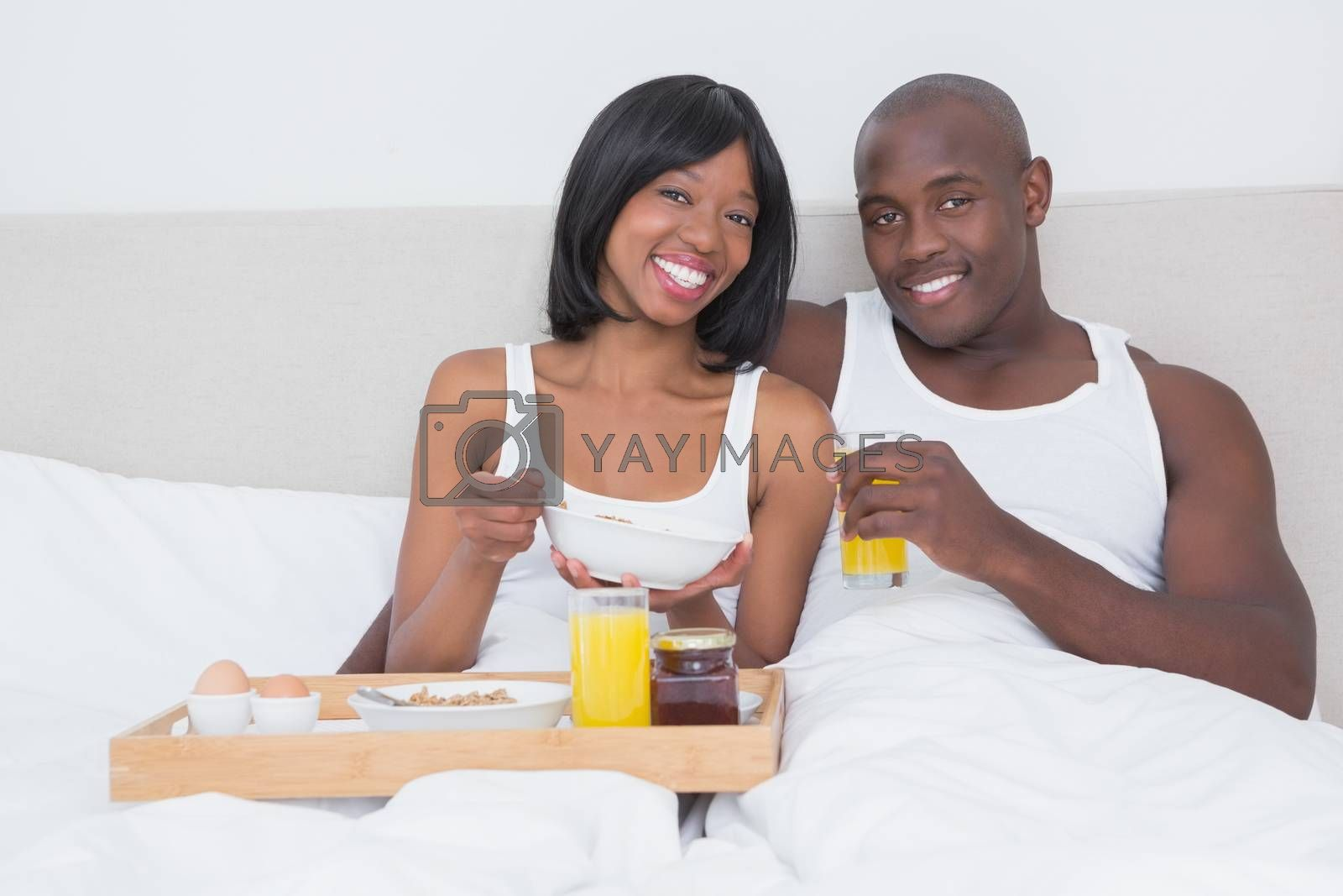 Royalty free image of Portrait of a pretty couple taking breakfast in bed together by Wavebreakmedia