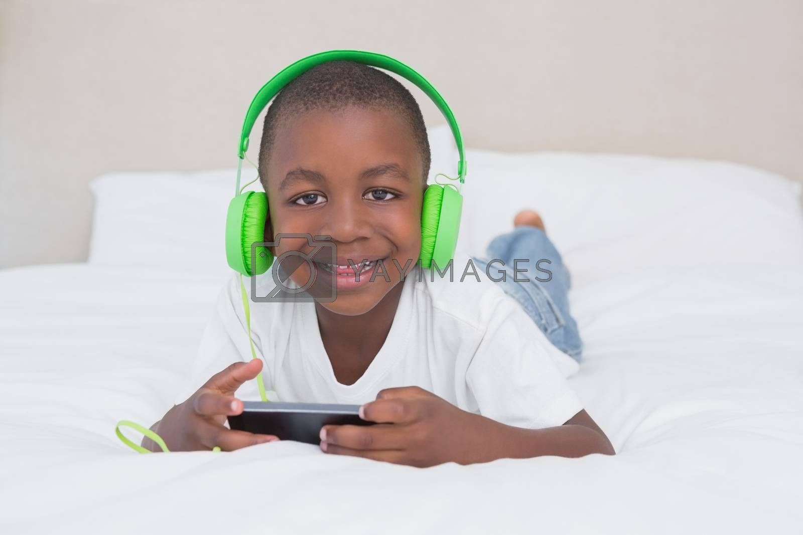 Royalty free image of Portrait of a pretty little boy using smartphone and listening music in bed by Wavebreakmedia