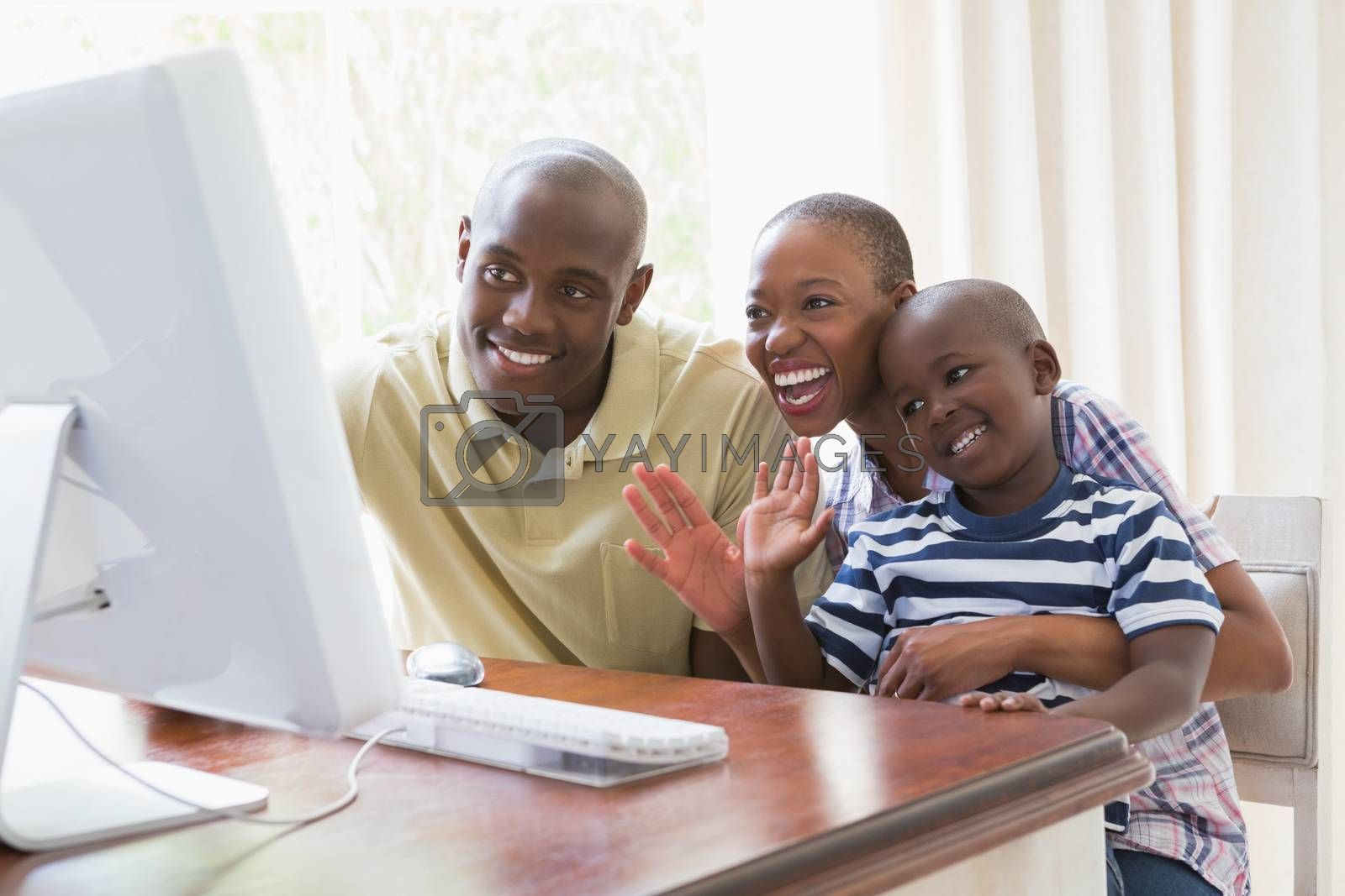 Royalty free image of Happy smiling family chattting with computer by Wavebreakmedia