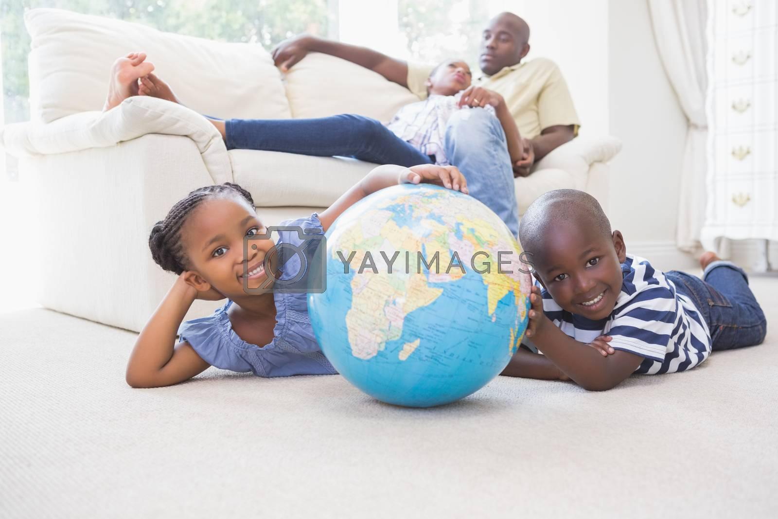 Royalty free image of Happy siblings using their globe  by Wavebreakmedia