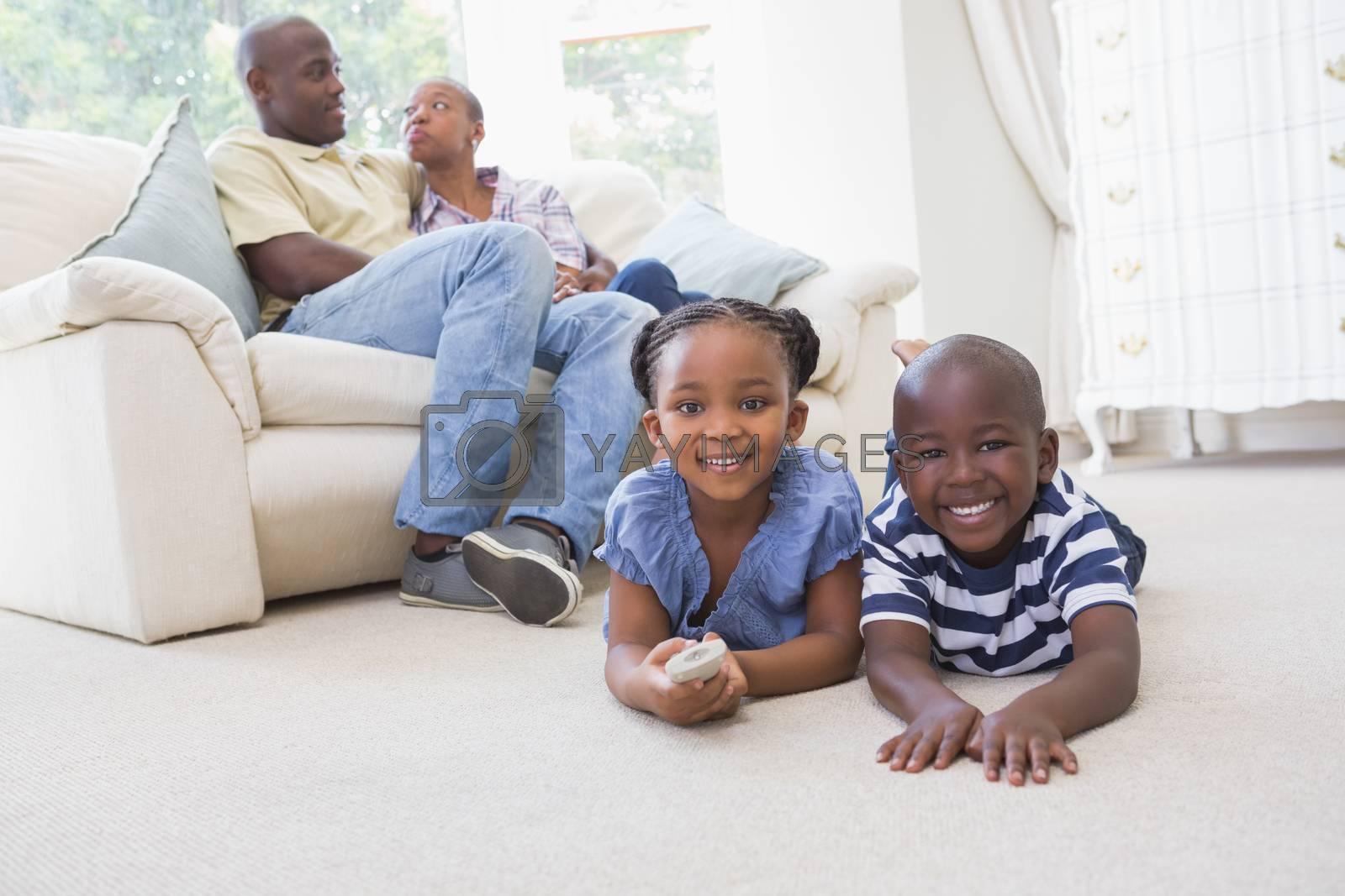 Royalty free image of Happy siblings sitting on the floor watching television by Wavebreakmedia