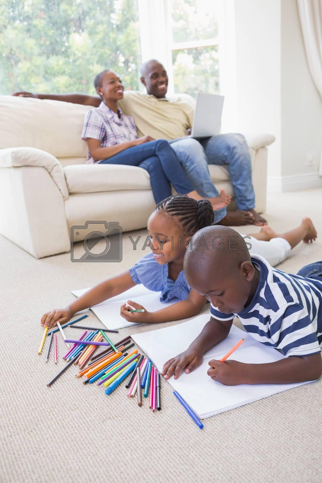 Royalty free image of Happy siblings on the floor drawing by Wavebreakmedia