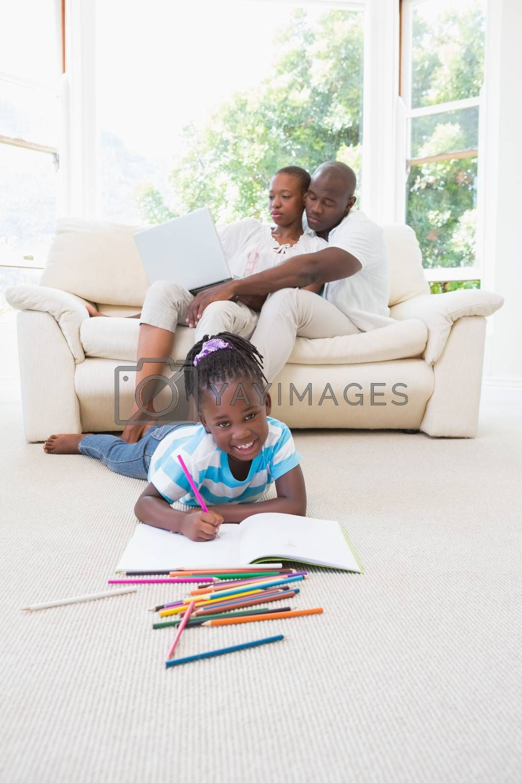 Royalty free image of Pretty couple using laptop on couch and their daughter drawing by Wavebreakmedia