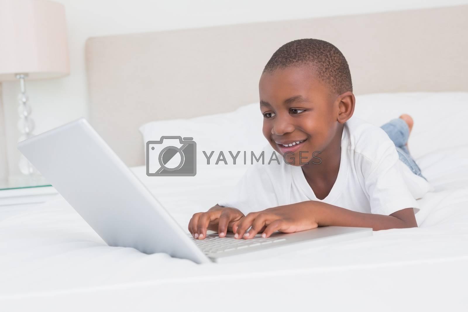 Royalty free image of Pretty little boy using laptop in bed  by Wavebreakmedia