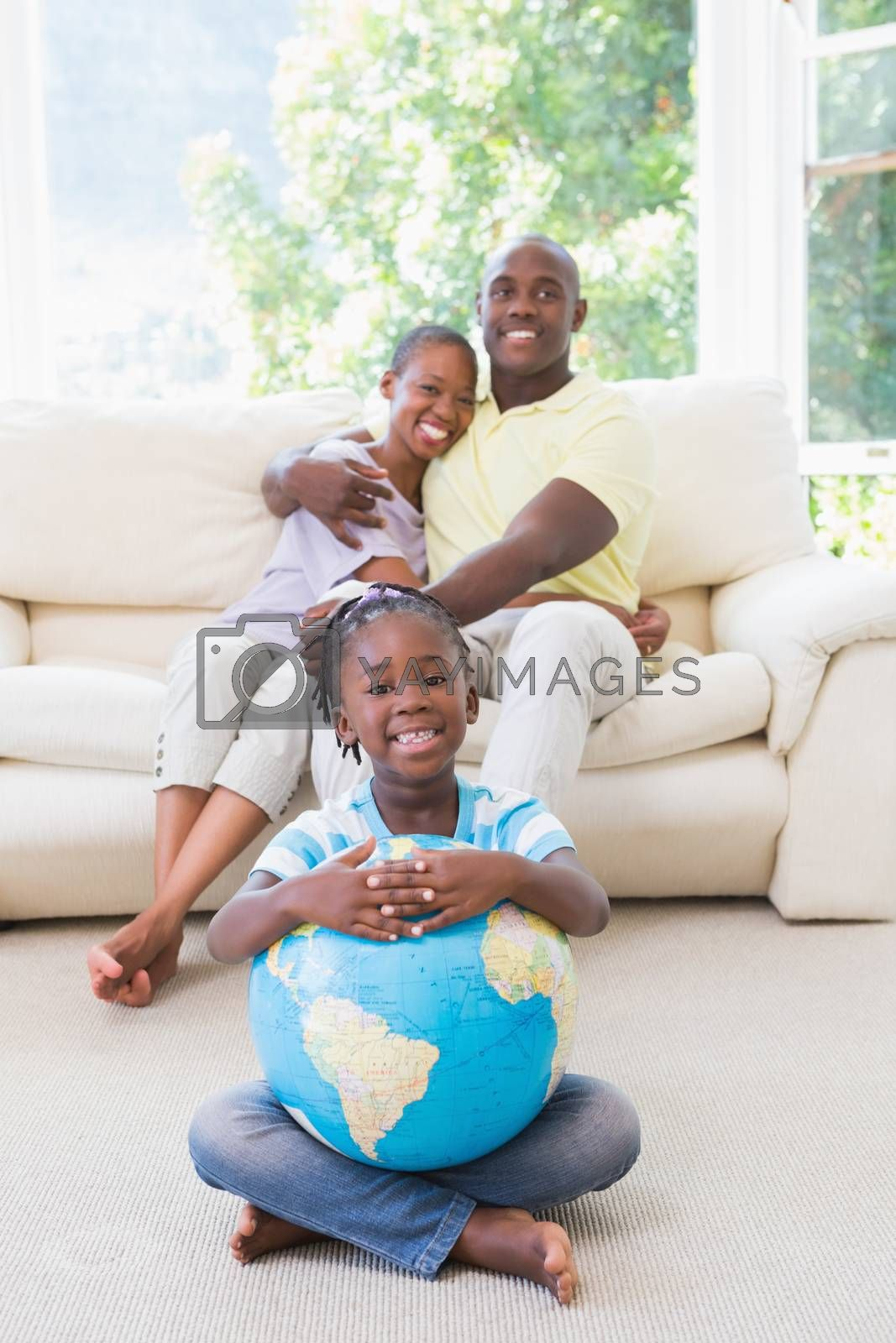 Royalty free image of Portrait of a happy smiling couple sitting on couch and daughter taking a globe  by Wavebreakmedia