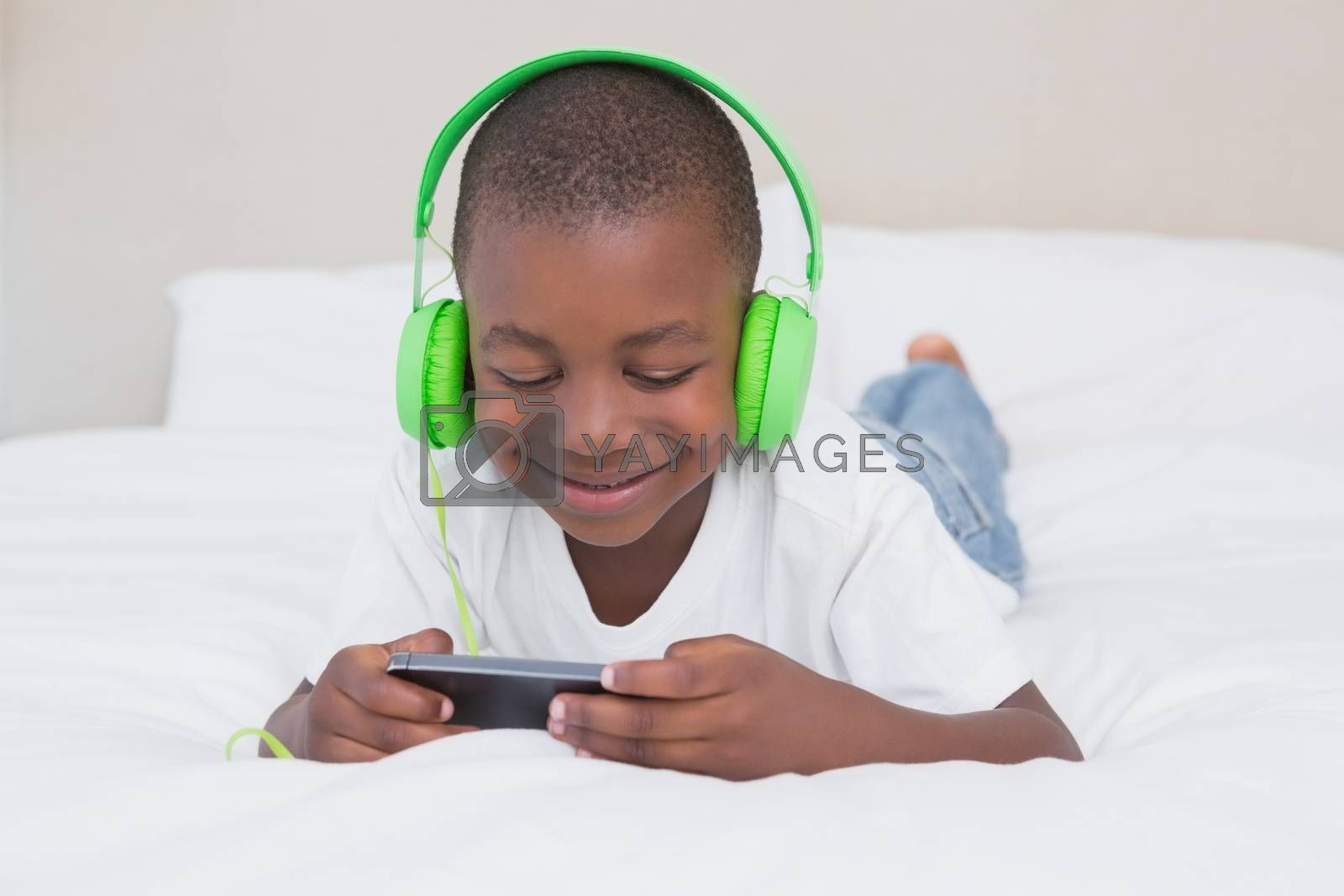 Royalty free image of Pretty little boy using smartphone and listening music in bed by Wavebreakmedia