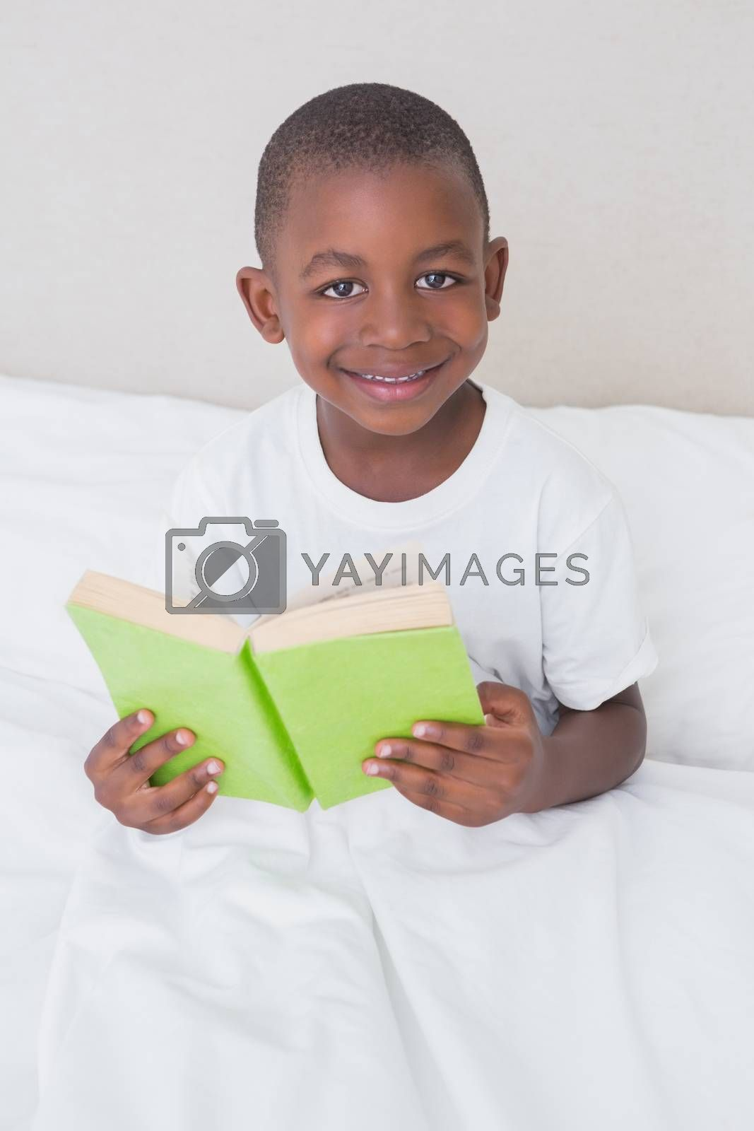 Royalty free image of Portrait of a little boy reading book in bed  by Wavebreakmedia