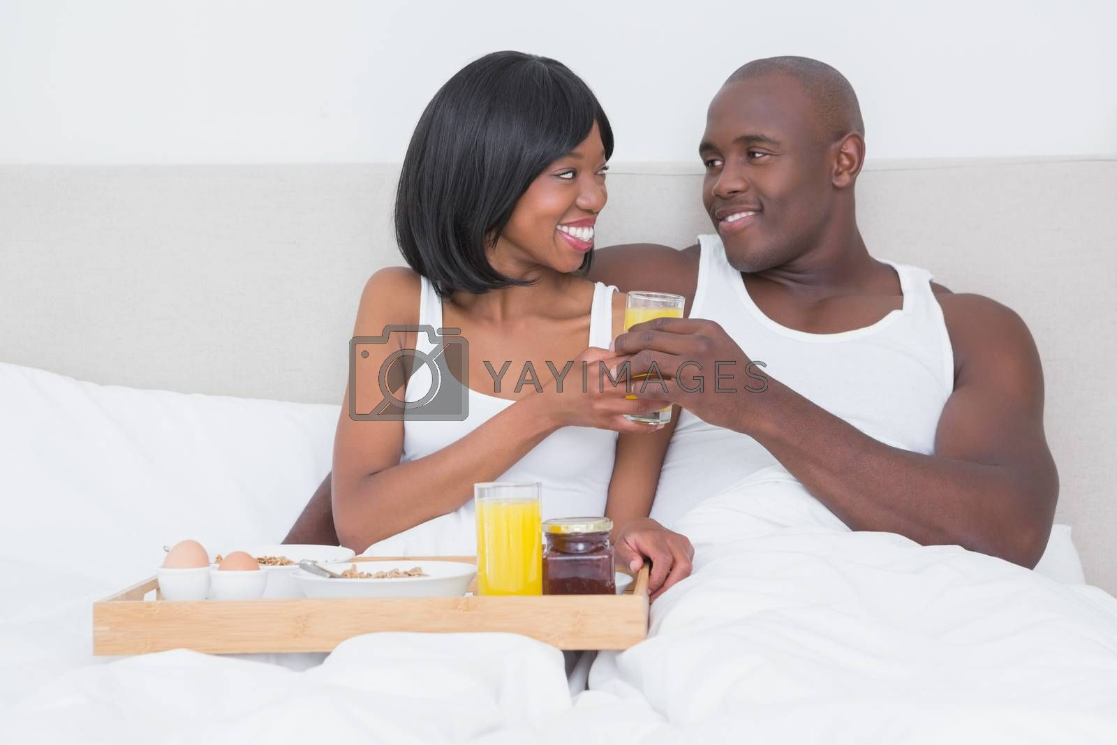 Royalty free image of Pretty couple taking breakfast in bed together by Wavebreakmedia
