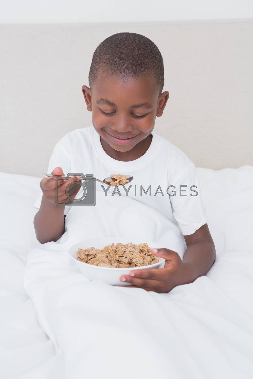 Royalty free image of Pretty little boy eating cereals in bed  by Wavebreakmedia