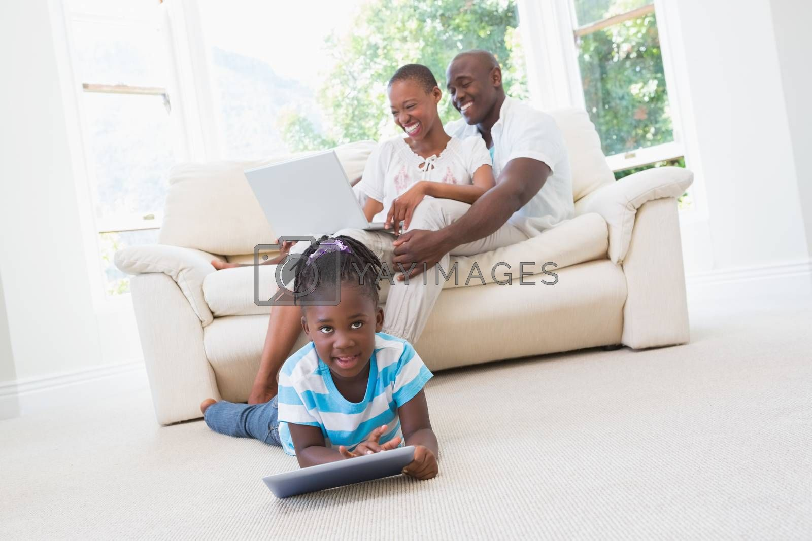 Royalty free image of Pretty couple using laptop on couch and their daughter using tablet  by Wavebreakmedia