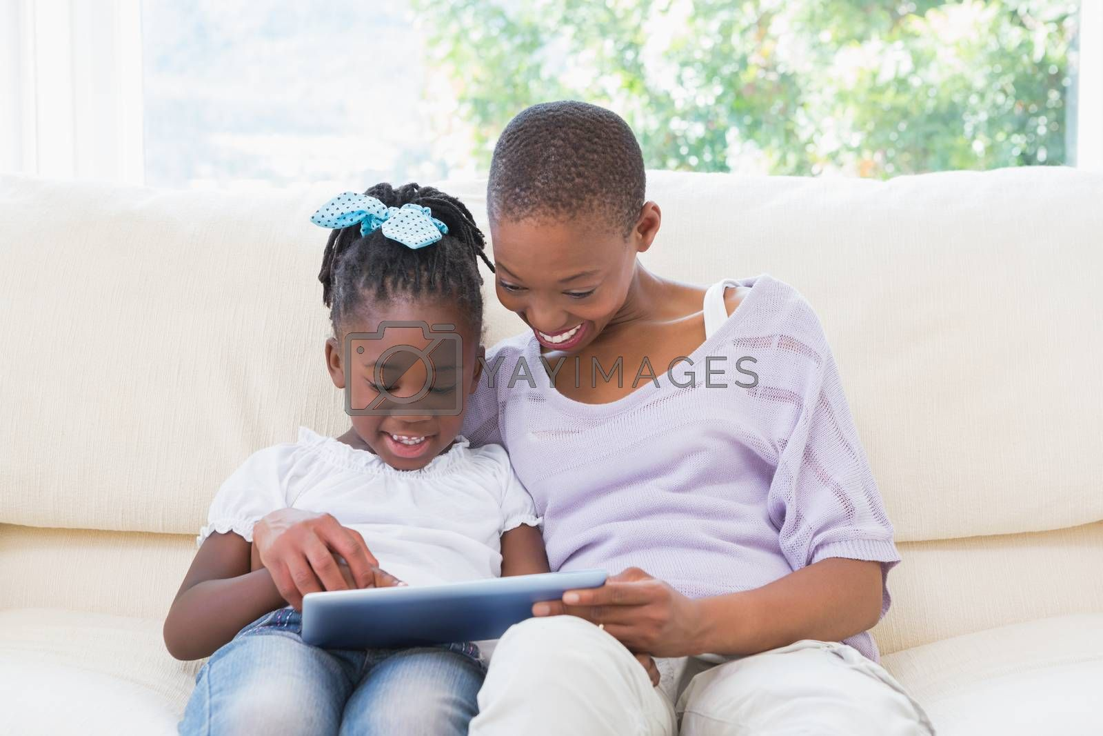 Royalty free image of Happy smiling mother using tablet with her daughter on couch  by Wavebreakmedia