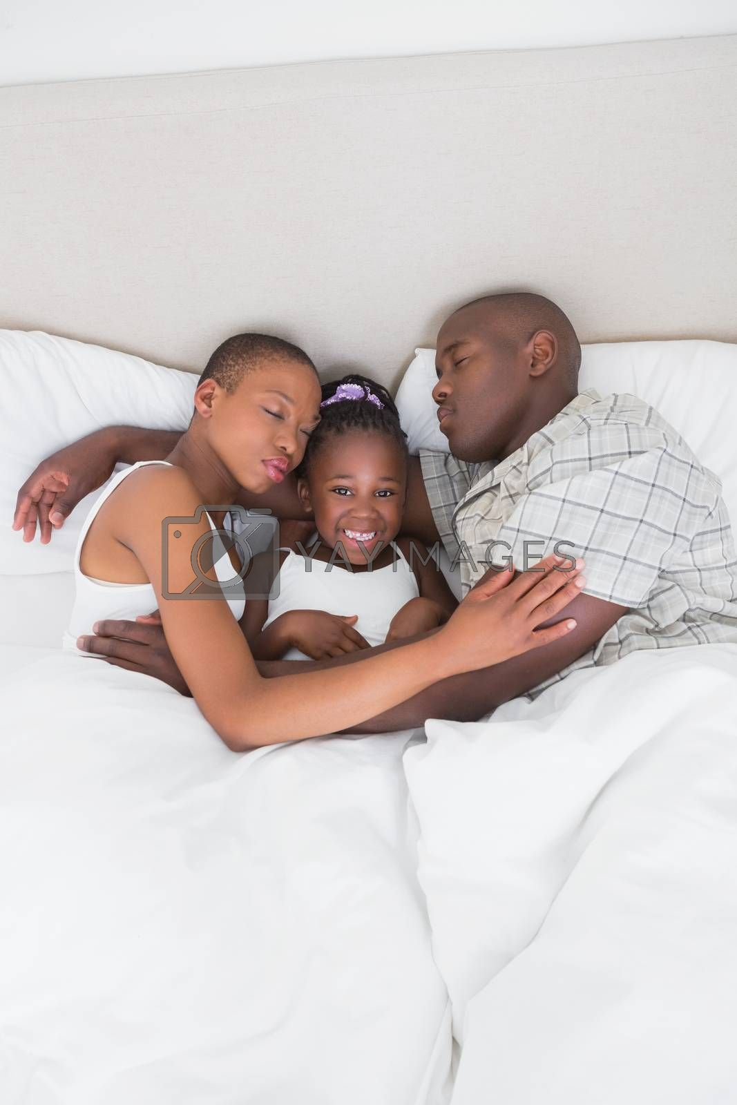 Royalty free image of Pretty couple sleeping with their daughter in their bed by Wavebreakmedia