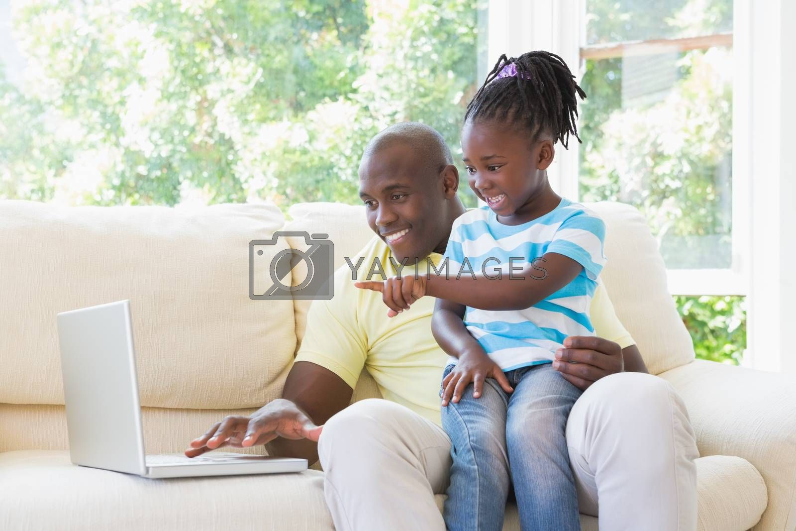 Royalty free image of Happy smiling father using laptop with her daughter on couch  by Wavebreakmedia