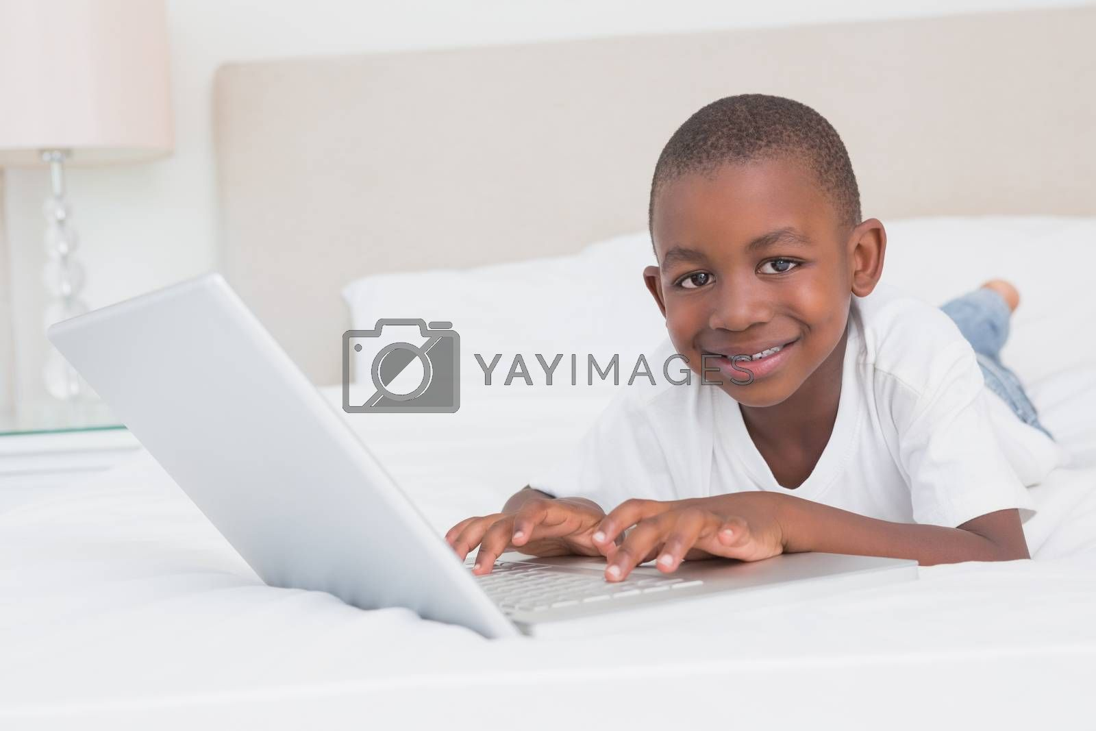Royalty free image of Portrait of a pretty little boy using laptop in bed by Wavebreakmedia