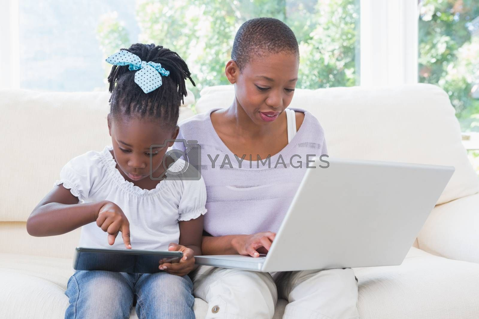Royalty free image of Happy smiling mother using laptop with her daughter using tablet on couch  by Wavebreakmedia