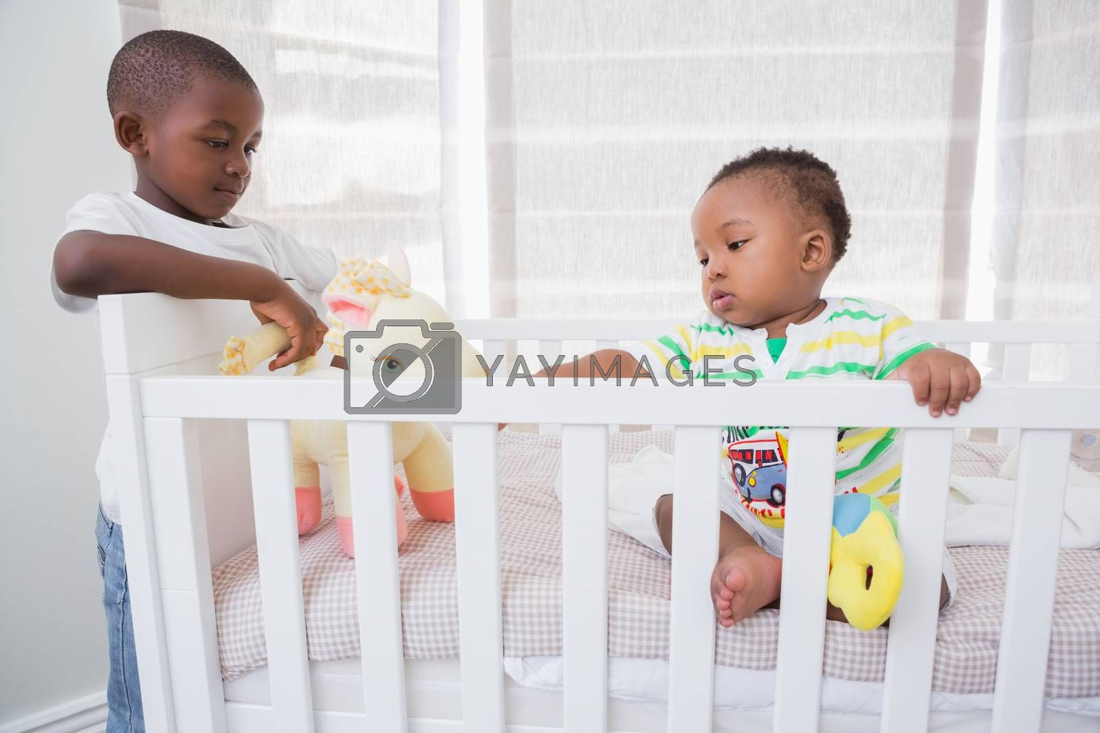 Royalty free image of Babyboy playing with his brother in his bed  by Wavebreakmedia