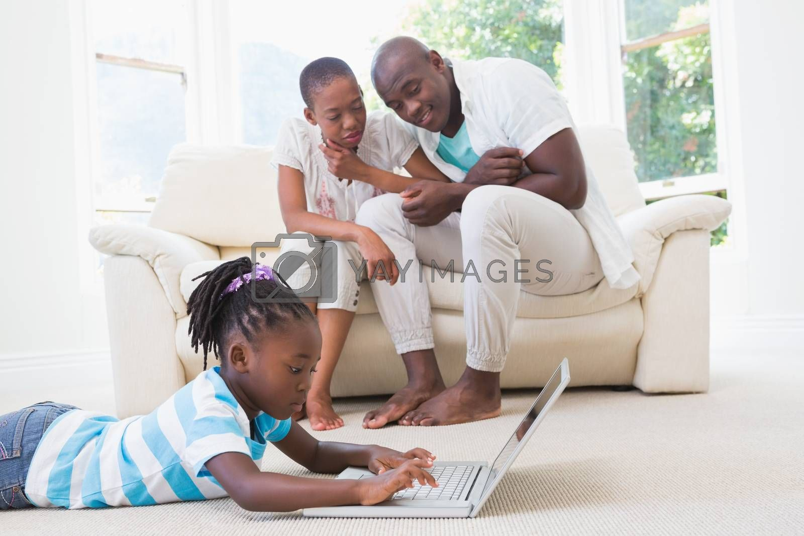 Royalty free image of Pretty couple sitting on couch and their daughter using laptop  by Wavebreakmedia