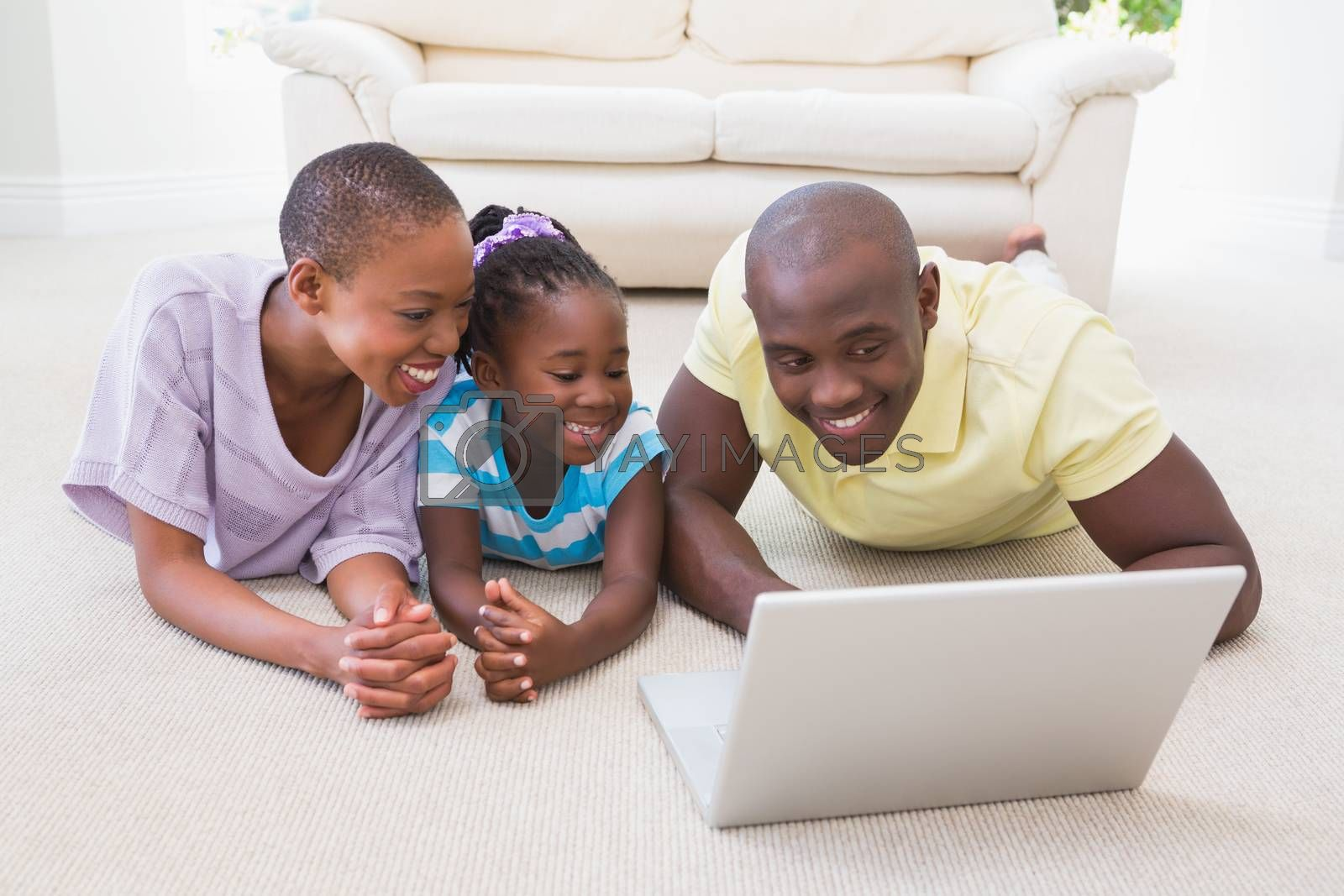 Royalty free image of Happy smiling couple using laptop with their daughter  by Wavebreakmedia